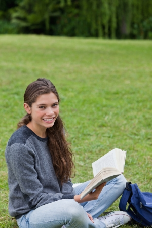 Young smiling girl sitting cross-legged on the grass while holding a book in a park photo
