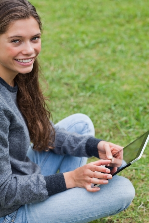 Young relaxed adult sitting down with her tablet computer while looking at the camera photo