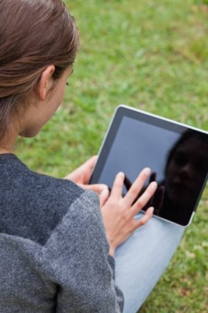 Rear view of a young girl using her tablet pc while sitting cross-legged in a park Stock Photo - 13670901