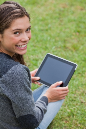 Young girl using her tablet computer while sitting on the grass and beaming photo