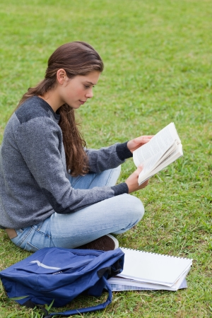 Young serious girl reading a book while sitting down with her notebook next to her Stock Photo