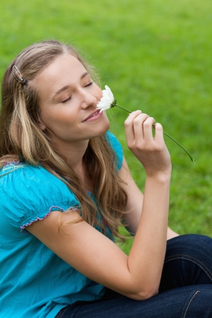 Young happy woman closing her eyes while sitting on the grass and smelling a flower Stock Photo - 13670336