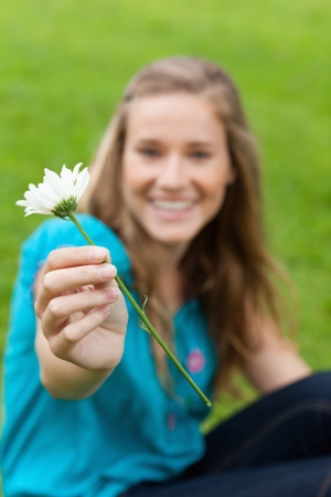 White flower held by a young smiling woman sitting in a park photo