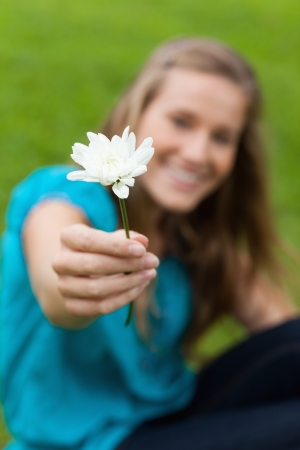 Beautiful white flower held by a smiling young girl in a park photo