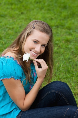 Smiling young girl holding a flower next to her face while sitting in a park photo