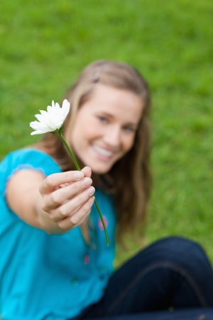 Beautiful white flower held by a young attractive girl sitting in the countryside photo