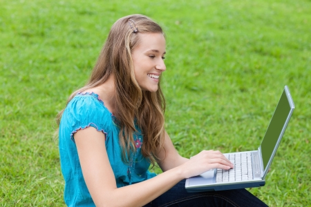 Young attractive girl looking at her laptop while sitting down on the grass in a park photo
