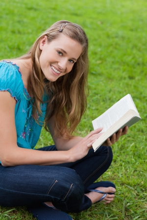 Young happy woman looking at the camera while reading a book in the countryside