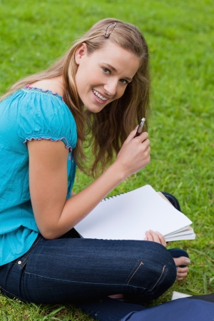 Smiling attractive girl holding her pen while looking straight at the camera photo