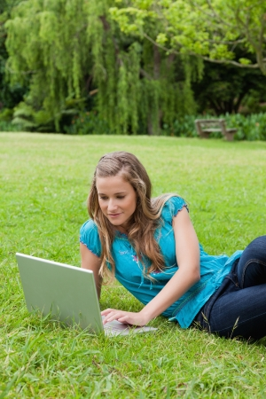Young calm girl lying on the side on the grass while working on her laptop in a park photo
