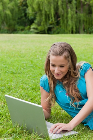 Smiling teenager lying on the grass in the countryside while typing on her laptop photo