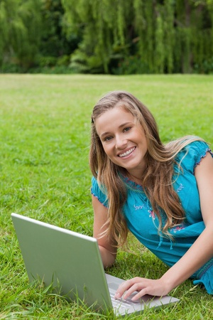 Young girl looking at the camera while typing on her laptop and showing a great smile Stock Photo - 13667296