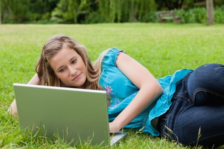 Calm student lying on the grass with her hand on head while working with her laptop photo