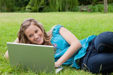 Young student lying on the side in a park while working on her laptop and smiling photo