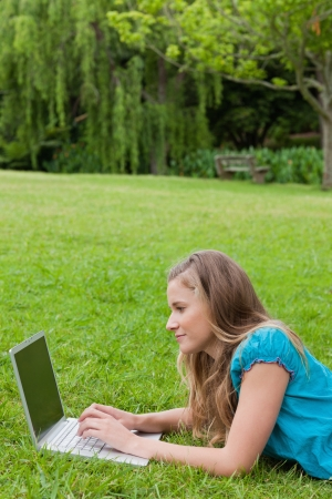 Side view of a young student using her laptop while lying on the grass in a park photo