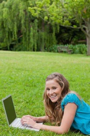 Young girl lying on the grass in a park while typing on her laptop and laughing photo
