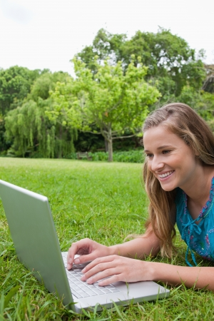 Young happy student using her laptop in the countryside while lying on the grass photo