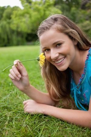 Young smiling woman smelling a yellow flower while lying down in the countryside photo