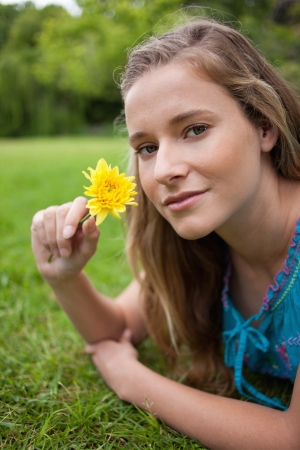 Young relaxed girl lying on the grass in the countryside while holding a yellow flower photo