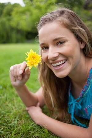 Smiling teenager holding a beautiful flower while lying on the grass in the countryside photo
