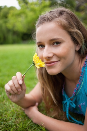 Happy student lying in a parkland while smelling a flower and looking at the camera photo