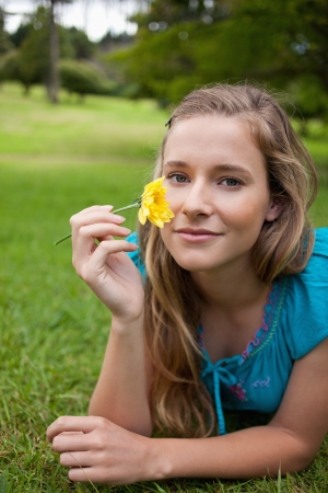 Young relaxed woman holding a beautiful yellow flower while lying in the countryside photo