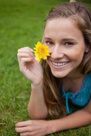 Smiling young girl showing a beautiful yellow flower while lying on the grass in a park Stock Photo - 13667804