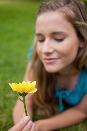 Beautiful yellow flower held by an attractive young girl photo