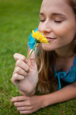 Young relaxed woman smelling a beautiful yellow flower while lying on the grass Stock Photo - 13667868