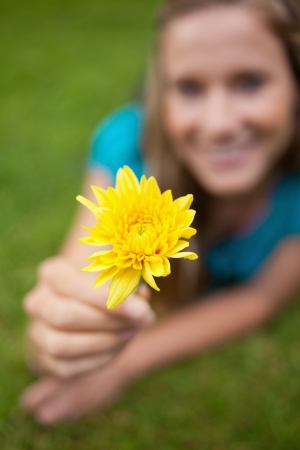 Beautiful yellow flower held by an attractive young girl lying in a park photo