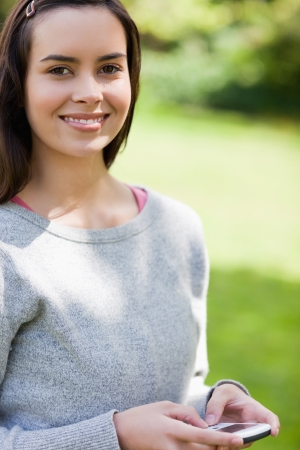 Young woman using her cellphone while standing in a park and looking at the camera photo