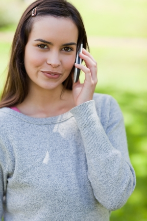 Peaceful young adult using her cellphone while standing in the countryside photo