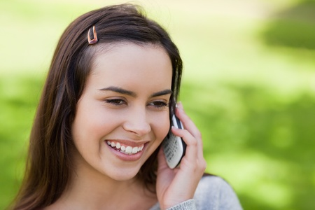 Smiling young woman using her mobile phone while standing in a parkland photo