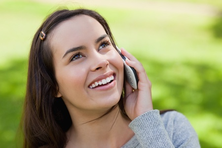 Young smiling woman talking with her cellphone while looking up in the countryside photo