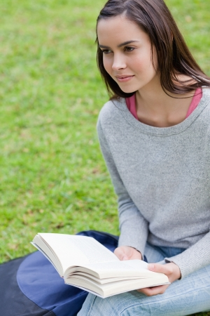 Young calm girl holding a book in a public garden while looking towards the side Stock Photo - 13670373