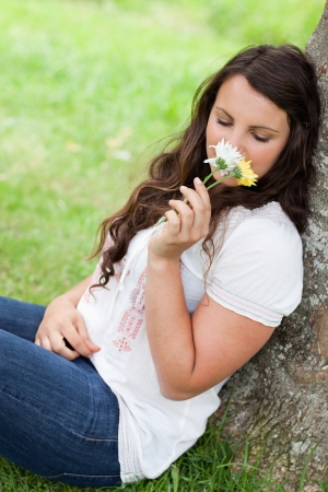 Young pretty woman leaning against a tree in the countryside while smelling flowers  photo