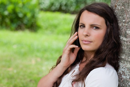 Young serious girl calling with her cellphone while sitting against a tree in a parkland photo