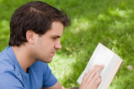 Young serious man reading a book while sitting down in the countryside photo