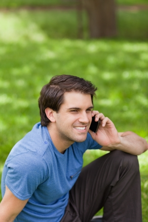 Young smiling man talking on the phone while sitting on the grass in a public garden photo