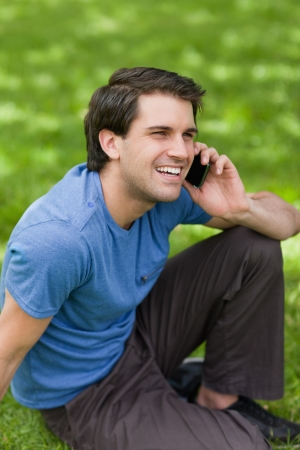 Young happy man laughing while sitting in the countryside and talking on the phone photo