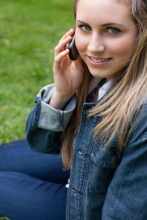 Young smiling girl using her mobile phone while sitting down in the countryside photo
