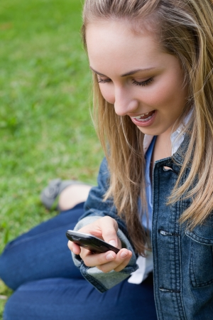 Attractive blonde teenage girl receiving a surprising text while sitting in a park photo