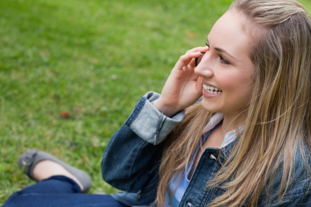 Young happy blonde girl calling with her mobile phone while sitting in the countryside photo