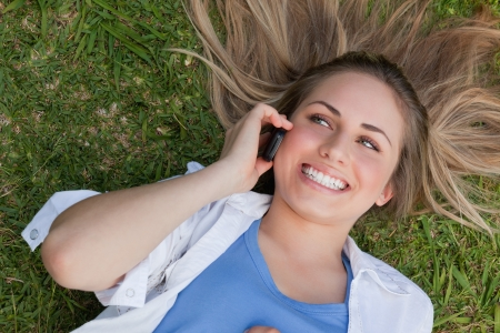 Young smiling woman lying on her back while calling while her mobile phone photo