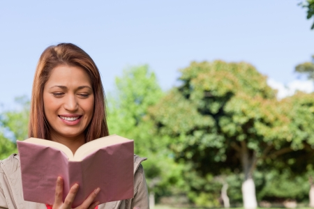 blissfully: Young woman blissfully reading the book in her hands while in a sunny area surrounded by trees Stock Photo