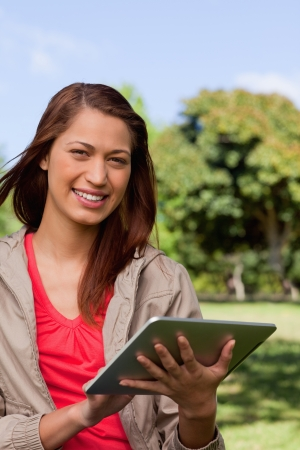 Young woman smiling and looking into the distance while she uses a tablet in a sunny park photo