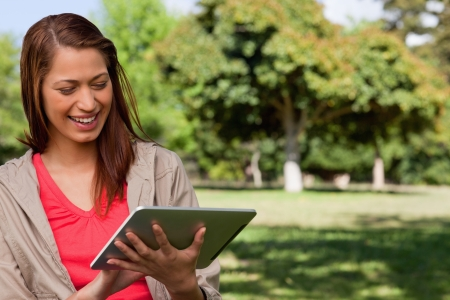 Young woman smiling enthusiastically while using a tablet in a sunny grassland area Stock Photo - 13668270