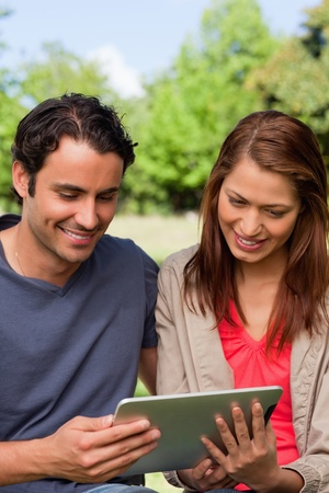 Man and his friend smiling as the watch something on a tablet in a sunny park photo