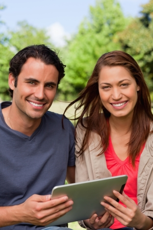 Man and a woman look ahead while holding a tablet in a sunny parkland environment photo