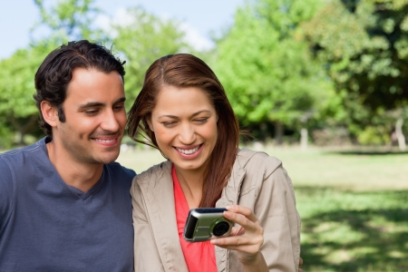 Woman and her friend looking at pictures on a camera in a bright park photo